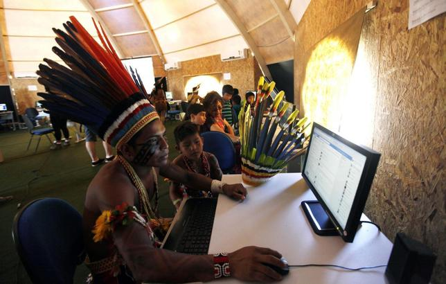 Brazilian indigenous people use computers inside a tent during the XII Games of the Indigenous People in Cuiaba November 13, 2013. REUTERS/Paulo Whitaker