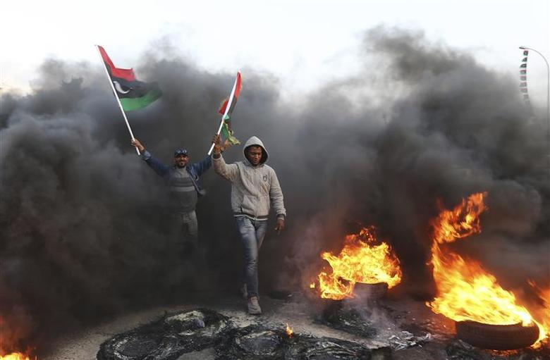 People hold Libyan flags amid smoke and fire after protesters set tyres on fire in a street during a demonstration against the General National Congress (GNC) in Benghazi February 21, 2014. REUTERS/Esam Omran Al-Fetori