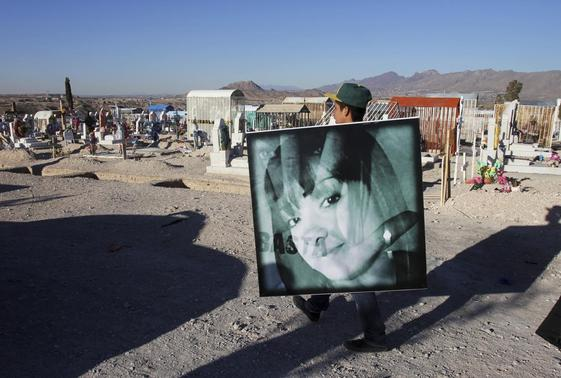 A man carries a photograph of Idaly Jauche Laguna while walking to her funeral in Ciudad Juarez December 27, 2013. REUTERS-Jose Luis Gonzalez