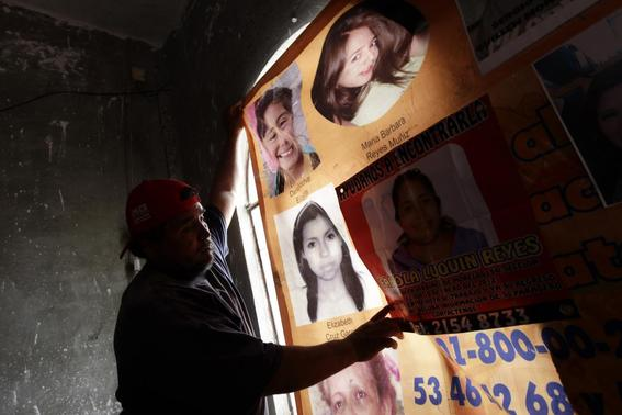 A man hangs up a banner showing photographs of missing and dead women in Ecatepec April 23, 2013. Abductions, rapes and murders of women have all soared with more women being killed in Mexico than ever before. REUTERS-Henry Romero