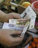 Продавец пересчитывает рублевые купюры на рынке в Москве 3 марта 2014 года. Рубль в минусе утром пятницы из-за политических рисков, связанных с конфликтом на Украине, и угрозы санкций западных стран экономического и гуманитарного характера против России. REUTERS/Maxim Shemetov