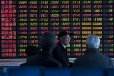 """Инвесторы у экрана с данными в брокерской фирме в Шанхае 4 марта 2014 года. Специализирующиеся на РФ фонды получили скромный приток за последнюю неделю за счет """"горячих"""" денег, невзирая на сильнейший со времен кризиса 2008 года обвал рынка за этот период и продолжающийся исход инвесторов с развивающихся площадок. REUTERS/Aly Song"""