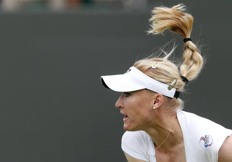 Elena Baltacha of Britain follows through on a serve to Flavia Pennetta of Italy during their women's singles tennis match at the Wimbledon Tennis Championships, in London June 24, 2013. REUTERS/Suzanne Plunkett