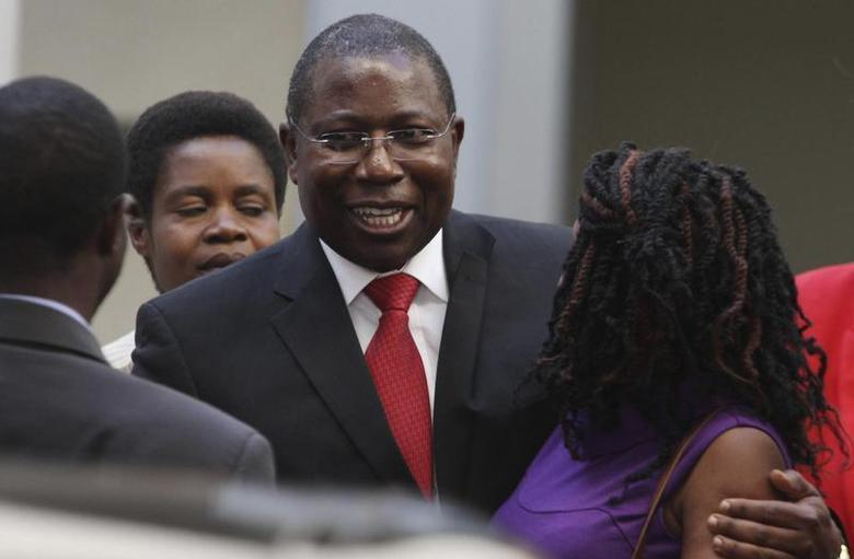 Energy and Power Development Minister Elton Mangoma (C) smiles with relatives at the High Court in Harare, June 28, 2011. REUTERS/Philimon Bulawayo