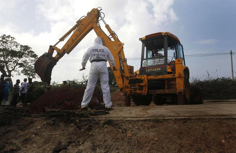 A police officer watches as an excavator digs up skeletons at a construction site in the former war zone in Mannar, about 327 km (203 miles) from the capital Colombo, January 16, 2014. REUTERS/Dinuka Liyanawatte