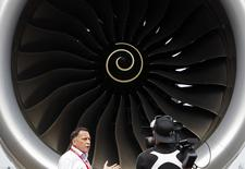 Journalists work next to the Rolls Royce engine of an Airbus A350 on display at the Singapore Airshow February 11, 2014. REUTERS/Edgar Su