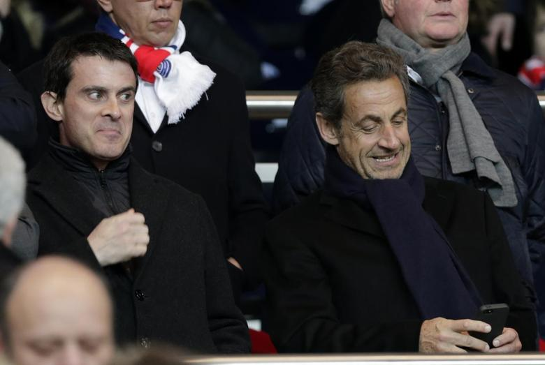 French Interior Minister Manuel Valls (L) and Former French President Nicolas Sarkozy (R) attend the French Ligue 1 soccer match between Paris Saint-Germain and Olympique Marseille at the Parc des Princes stadium in Paris, March 2, 2014. REUTERS/Philippe Wojazer