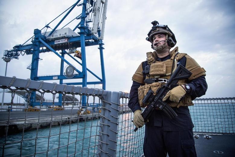 A guard looks on as the Norwegian frigate ''Helge Ingstad'' leaves the port of Limassol in Cyprus December 28, 2013. The vessel is part of the Danish-Norwegian force that will transport Syria's chemical agents out of the country to destruction. REUTERS/Lars Magne Hovtun/Norwegian Armed Forces/NTB Scanpix