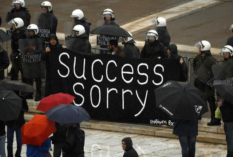 Workers, who lost their jobs recently, hold a banner outside the parliament during an anti-austerity protest in Athens November 6, 2013. REUTERS/Yannis Behrakis