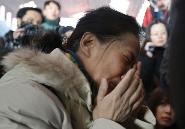 A relative of a passenger onboard Malaysia Airlines flight MH370 cries, surrounded by journalists, at the Beijing Capital International Airport in Beijing March 8, 2014. REUTERS/Kim Kyung-Hoon