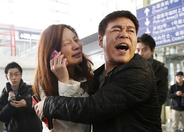 A relative (woman in white) of a passenger onboard Malaysia Airlines flight MH370 cries as she talks on her mobile phone at the Beijing Capital International Airport March 8, 2014. REUTERS/Kim Kyung-Hoon
