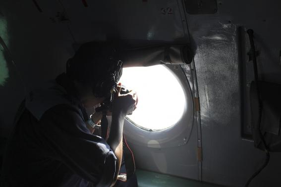A Vietnamese Air Force officer takes photos from a search and rescue aircraft in the search area for a missing Malaysia Airlines plane, 250 km from Vietnam and 190 km from Malaysia, in this handout photo from Thanh Nien Newpaper taken March 8, 2014. Mandatory Credit REUTERS-Trung Hieu-Thanh Nien Newspaper