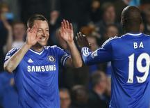 Chelsea's John Terry (L) celebrates with Demba Ba after defeating Tottenham Hotspur in their English Premier League soccer match at Stamford Bridge in London March 8, 2014. REUTERS/Eddie Keogh