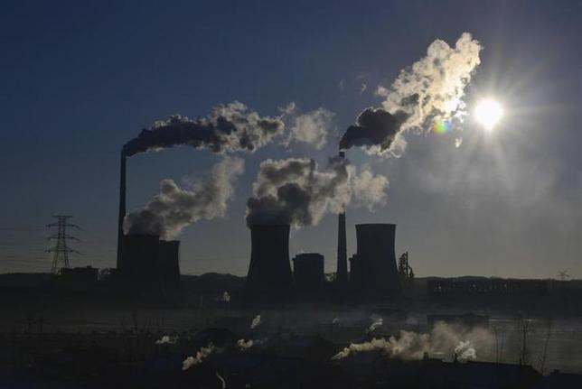 Smoke rises from chimneys and cooling towers of a thermal power plant during sunrise in Fushun, Liaoning province March 6, 2014. REUTERS/Stringer