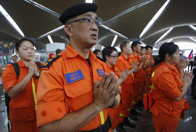 Rescue workers from a Buddhist organization pray during multi-religion mass prayers for the passengers of Malaysian Airlines flight MH370 at Kuala Lumpur International Airport in Sepang March 9, 2014. REUTERS/Edgar Su