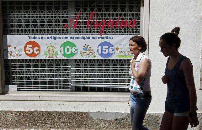 Women walk past a shop window announcing sale prices along a street in Mafra, north of Lisbon August 20, 2013. REUTERS/Jose Manuel Ribeiro