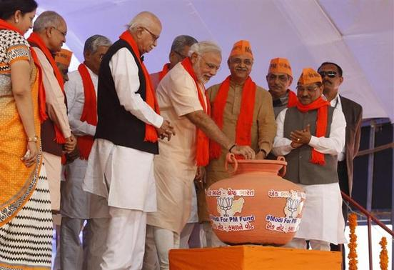 Hindu nationalist Narendra Modi (C), prime ministerial candidate for Bharatiya Janata Party (BJP) and Gujarat's chief minister, drops a 1000 rupee note in a pitcher marked 'Modi-for-PM fund' after he inaugurated a new office building for the party in Koba near Gandhinagar in Gujarat February 10, 2014. REUTERS/Amit Dave/Files