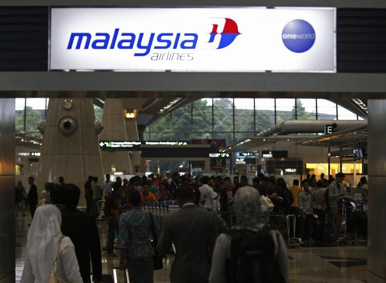 Passengers queue up at the Malaysia Airlines ticketing booth at the Kuala Lumpur International Airport in Sepang March 9, 2014. REUTERS/Edgar Su