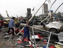 People look at the damage and wreckage at the site of a suicide attack in the city of Hilla March 9, 2014. REUTERS/Habib