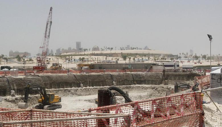Bulldozers operate on a road under construction near Doha Towers June 25, 2013. REUTERS/Mohammed Dabbous