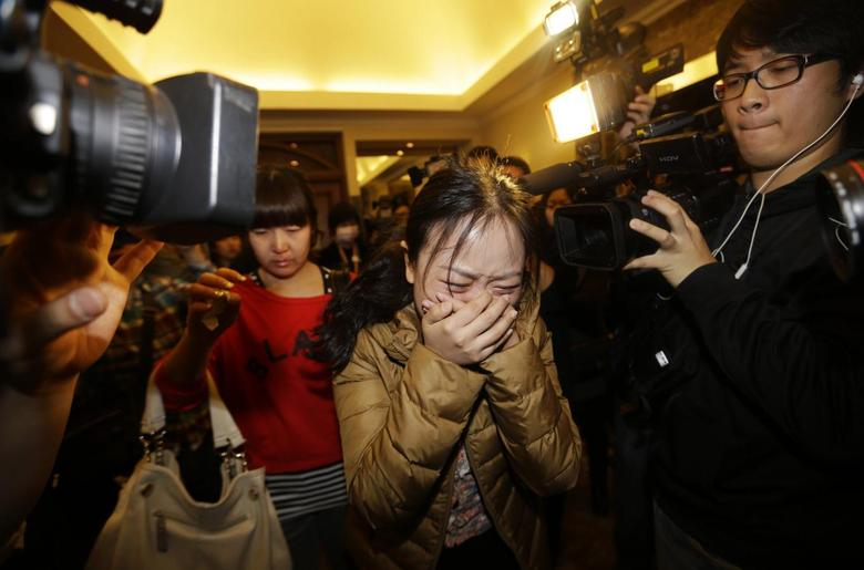 A relative (front) of a passenger of Malaysia Airlines flight MH370 cries as she walks past journalists at a hotel in Beijing March 9, 2014. REUTERS/Jason Lee