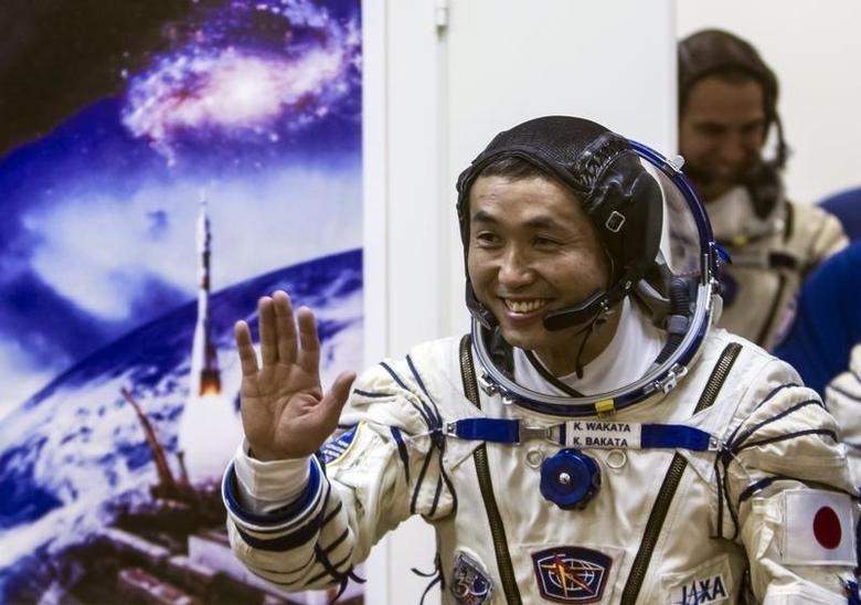 International Space Station (ISS) crew member Japanese astronaut Koichi Wakata waves after donning a space suit shortly before the blast off for the ISS, at the Baikonur cosmodrome November 7, 2013. REUTERS/Shamil Zhumatov