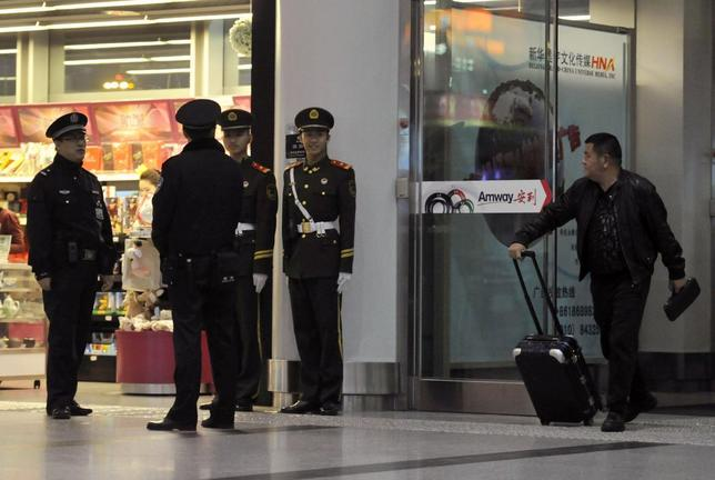 A passenger (R) looks at police officers (L) and paramilitary policemen on duty at the Beijing Capital International Airport after Malaysia Airlines flight MH370 went missing, in Beijing, March 9, 2014. REUTERS/Stringer