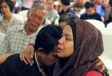صورة لأقارب بعض ركاب الطائرة الماليزية المفقودة يبكون يوم الاحد. تصوير رويترز.