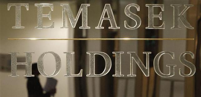 A staff member is reflected in a Temasek Holdings logo at their headquarters before the presentation of Temasek's annual review in Singapore, in this September 17, 2009 file picture. REUTERS/Vivek Prakash/Files