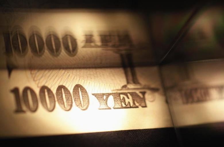 Light is cast on a Japanese 10,000 yen note as it's reflected in a plastic board in Tokyo, in this February 28, 2013 picture illustration. REUTERS/Shohei Miyano