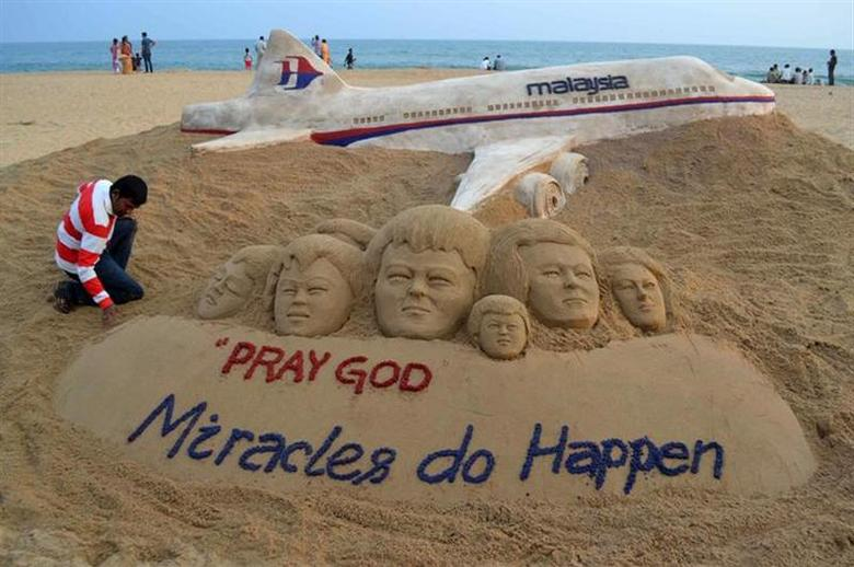 Indian sand artist Sudarshan Patnaik applies the final touches to a sand art sculpture he created wishing for the well being of the passengers of Malaysian Airlines flight MH370, on a beach in Puri, Odisha, March 9, 2014. REUTERS/Stringer