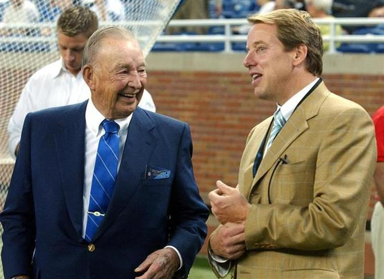William Clay Ford Sr. (L) chats on the sidelines with his son Bill Ford Jr. before the start of the Lions season home opener against the Houston Texans at Ford Field in Detroit, Michigan September 19, 2004. REUTERS/Rebecca Cook RC/Files