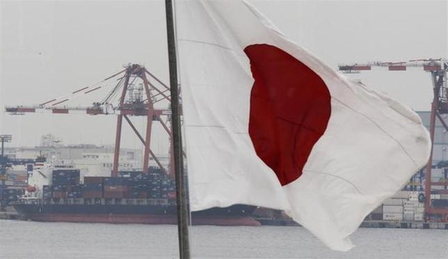 A cargo ship is seen behind Japan's national flag at an industrial port in Tokyo March 8, 2012. REUTERS/Kim Kyung-Hoon/Files