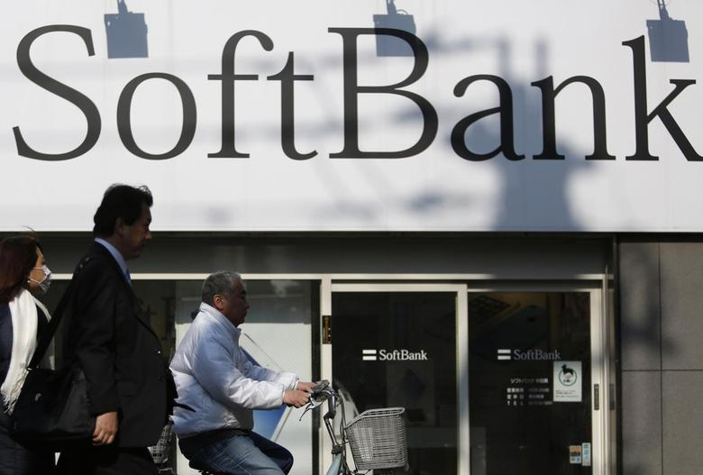 Pedestrians walk in front of a SoftBank Corp logo outside its branch in Tokyo February 25, 2014.REUTERS/Yuya Shino