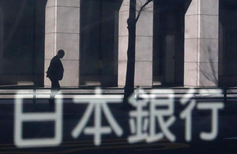 A man walking past a building is reflected in a sign board of the Bank of Japan building in Tokyo January 22, 2014. REUTERS/Yuya Shino