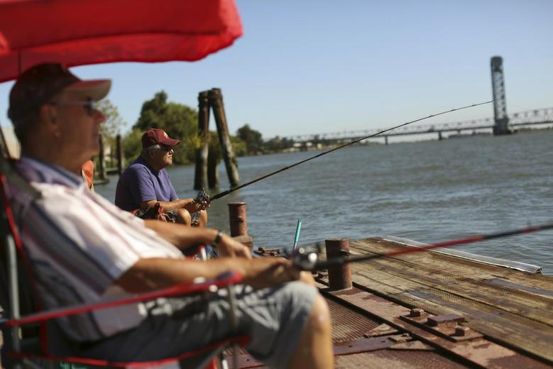 Retirees Gene Bloczynski (L) and Eric Vannieuwburg fish from a public dock on the Sacramento River in the Sacramento San Joaquin River Delta in Rio Vista, California September 4, 2013. REUTERS/Robert Galbraith