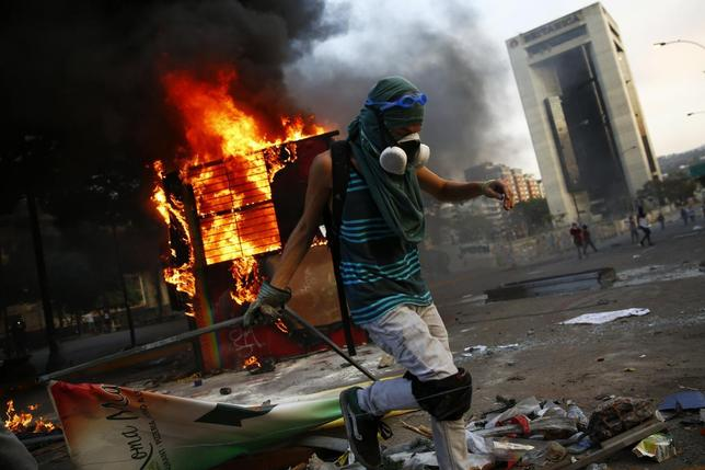 An anti-government protester sets up a barricade next to a burning kiosk during a protest at Altamira square in Caracas March 9, 2014. REUTERS/Jorge Silva
