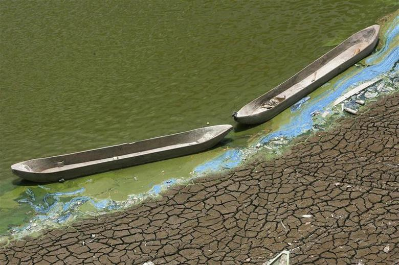 Wooden boats sit at the base of a dried-up reservoir, due to the long dry season, at Kedung Sumber village, near Bojonegoro Indonesia's East Java province, in this October 16, 2013 file photo. REUTERS/Sigit Pamungkas/Files