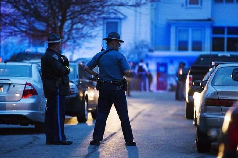 Law enforcement officials stand at the scene on Franklin St. as the search for Dzhokhar Tsarnaev, the surviving suspect in the Boston Marathon bombings, comes to an end in Watertown, Massachusetts April 19, 2013. REUTERS/Lucas Jackson