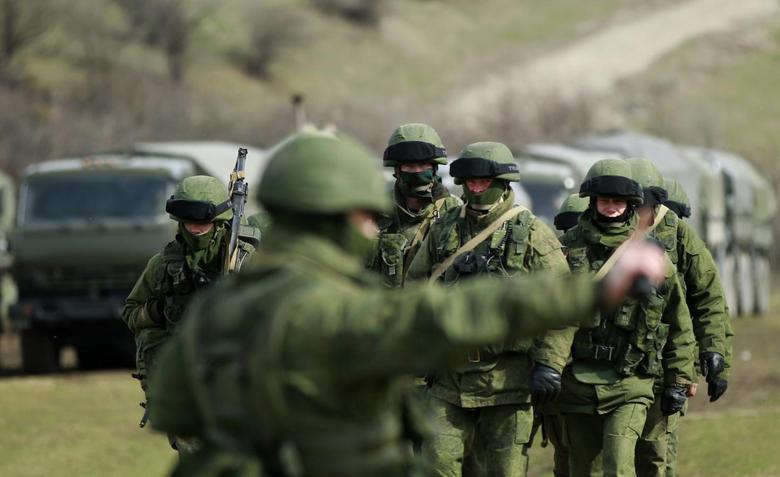 Armed men, believed to be Russian servicemen, march outside an Ukrainian military base in the village of Perevalnoye near the Crimean city of Simferopol March 10, 2014. REUTERS/David Mdzinarishvili