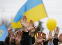 Сторонники единой Украины на митинге в Симферополе 9 марта 2014 года. Минфин страны убежден в способности новых властей Украины избежать коллапса за счет радикальных реформ и перекройки бюджета. REUTERS/Thomas Peter