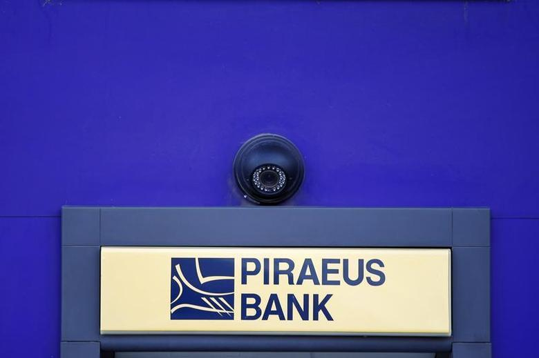 A surveillance camera is seen over the logo of Piraeus Bank on an ATM machine outside one of its branches in Bucharest April 18, 2013. REUTERS/Bogdan Cristel