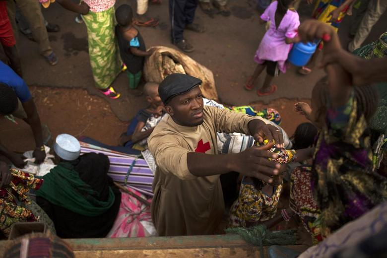 Father Bernard Kenvi (C) helps a Muslim child climb down from an open truck in the town of Bossemptele, west of Central African Republic March 8, 2014, as a group of mostly women and children flee sectarian violence in a safer container truck in a convoy escorted by African Union (AU) peacekeepers. REUTERS/Siegfried Modola