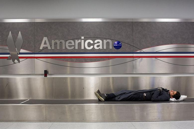 A man sleeps on a conveyer belt under an American Airlines logo at John F. Kennedy International Airport in New York January 22, 2014. REUTERS/Andrew Kelly