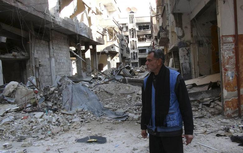 A man stands amid the rubble of damaged buildings at the Palestinian refugee camp of Yarmouk, south of Damascus February 18, 2014. REUTERS/Stringer