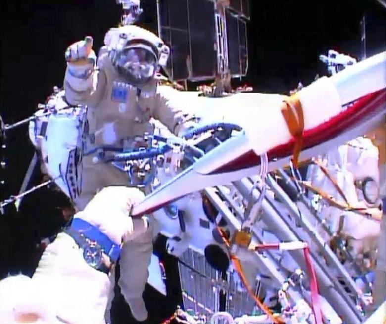 Russian astronaut Oleg Kotov holds an Olympic torch as he takes it on a spacewalk as Russian astronaut Sergei Ryazansky gives instructions outside the International Space Station in this still image taken from video courtesy of NASA TV, November 9, 2013. REUTERS/NASA TV/Handout via Reuters
