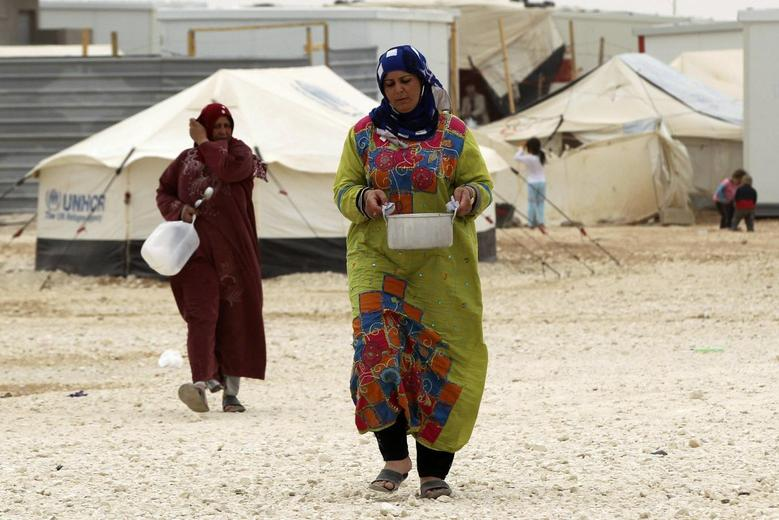 A Syrian woman refugee carries a pot of cooked food during International Women's Day at the al-Zaatri refugee camp in the Jordanian city of Mafraq, near the border with Syria, March 8, 2014. REUTERS/Muhammad Hamed