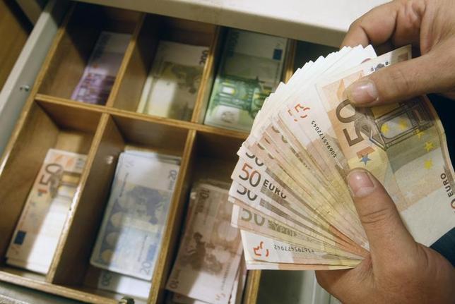 A teller counts euro banknotes inside a National Bank of Greece branch in Athens February 10, 2010. REUTERS/John Kolesidis