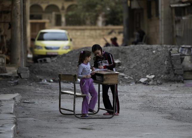 Girls write on a school desk as they stand along a street in Deir al-Zor, eastern Syria, February 23, 2014. REUTERS/Khalil Ashawi