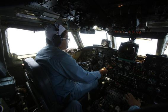 Caption Dinh Van Qua operates on the cockpit of an aircraft AN-26 belonging to the Vietnam Air Force during a search and rescue mission off Vietnam's Tho Chu island March 10, 2014. REUTERS/Kham